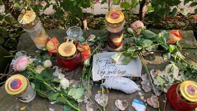 Blumen und Kerzen auf Steinen in der Simmlerstraße