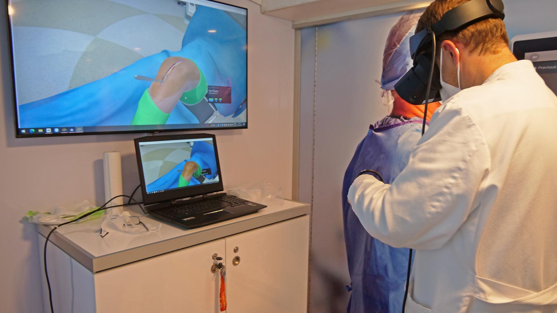 Ein Mann steht mit einer VR-Brille vor einem Bildschirm, auf dem ein offenes Knie zu sehen ist.