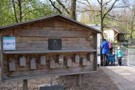 """Ein Holzhäuschen mit der Aufschrift """" Herzlich Willkommen im Wildpark"""" steht im Vordergrund, im Hintergrund sind Menschen und ein Gehege mit Tieren."""