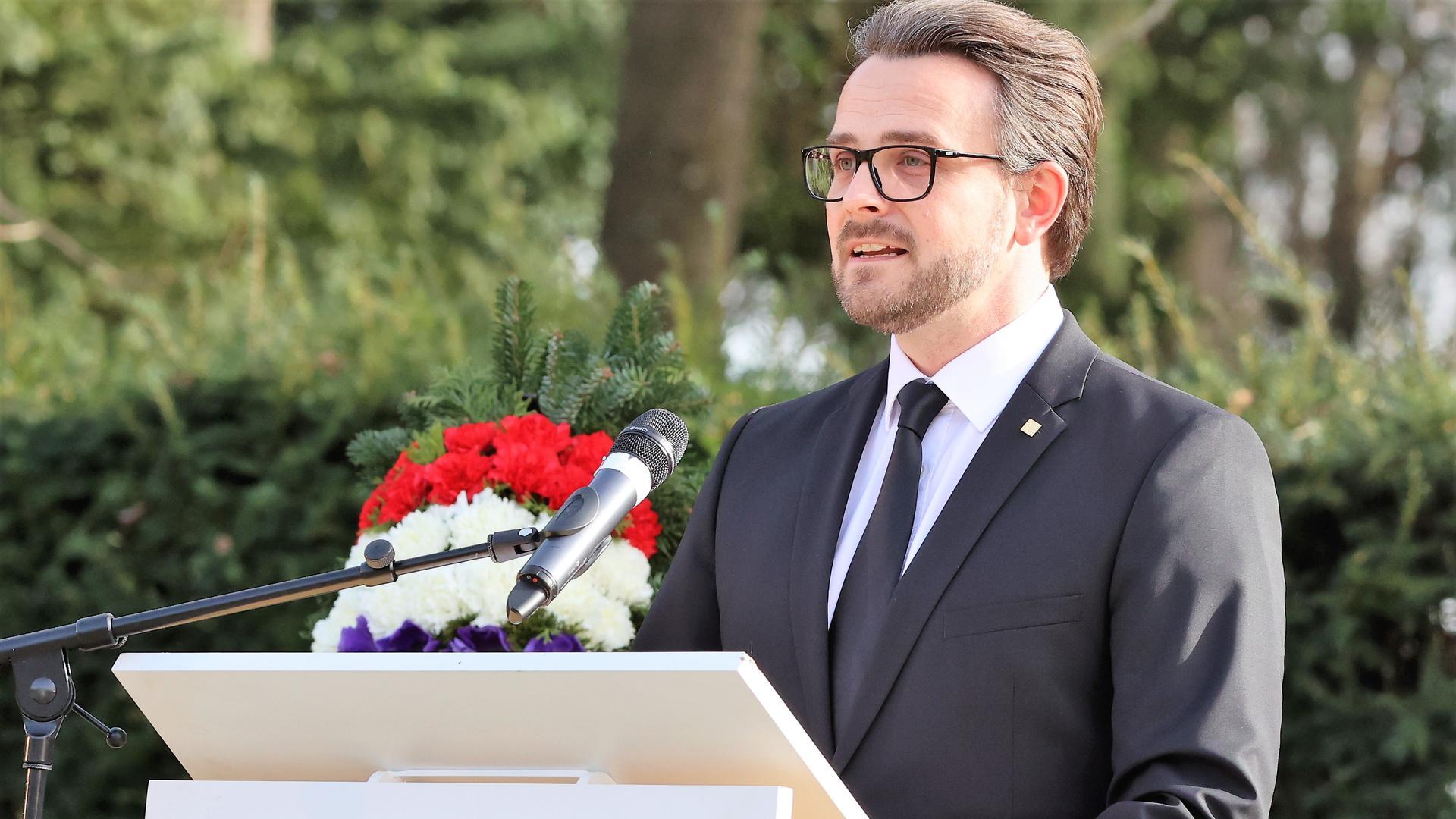 In dunklem Anzug vor einem großen Kreuz aus Stein: Pforzheims Oberbürgermeister Peter Boch (CDU) spricht am Dienstagnachmittag bei der offiziellen Gedenkveranstaltung der Stadt Pforzheim auf dem Hauptfriedhof