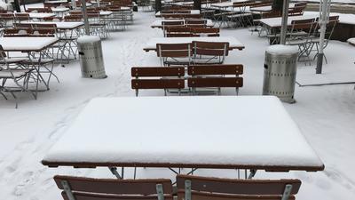 Mehrere Tische und Stühle, Außenbereich eines gastronomischen Betriebs, alles ist bedeckt von einer Schneeschicht.