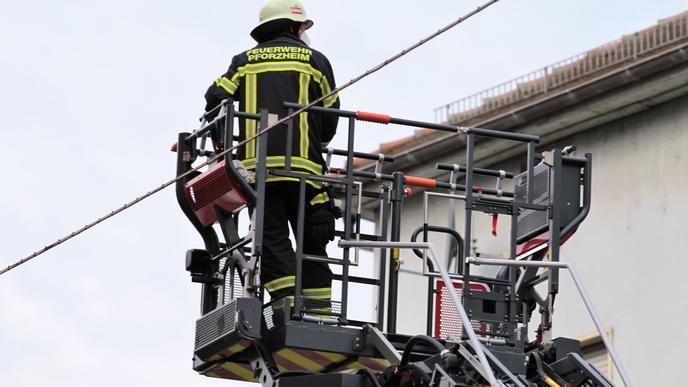 Ein Feuerwehrmann am Mittwochmorgen auf einer Drehleiter an einem Gebäude in der Pforzheimer Leopoldstraße.