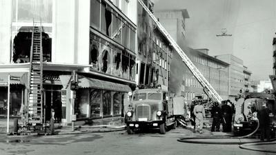 Schwarz-weiß-Foto eines Brands: Feuerwehr mit Leitern vor einem Haus mit geborstenen Fensterscheiben.
