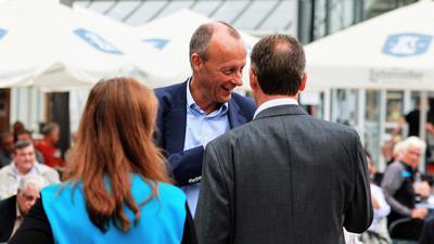CDU-Politiker Friedrich Merz vor seiner Rede im Enzauen-Biergarten in Pforzheim. Von hinten: Bundestagsabgeordneter Gunther Krichbaum und Stadträtin Oana Krichbaum.