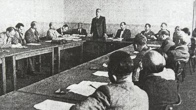 Mehrere Männer sitzen um einen Tisch, schwarz-weiß-Aufnahme