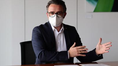 Mit Maske gestikulierend: Pforzheims Oberbürgermeister Peter Boch (CDU) gestikuliert an einem Tisch.