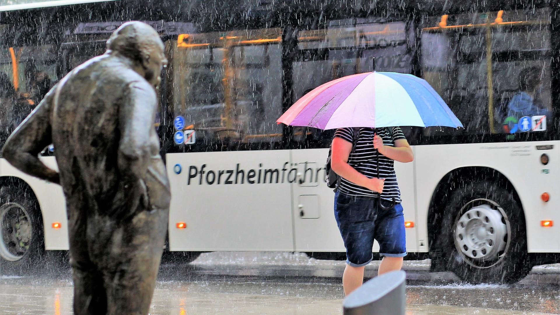 """Eine junge Frau schützt sich in der Pforzheimer Leopoldstraße mit einem Schirm gegen den prasselnden Regen. Stoisch steht wie immer die Skulptur """"Der Dicke"""""""