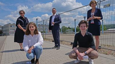 Fünf Personen stehen vor einem Bauzaun