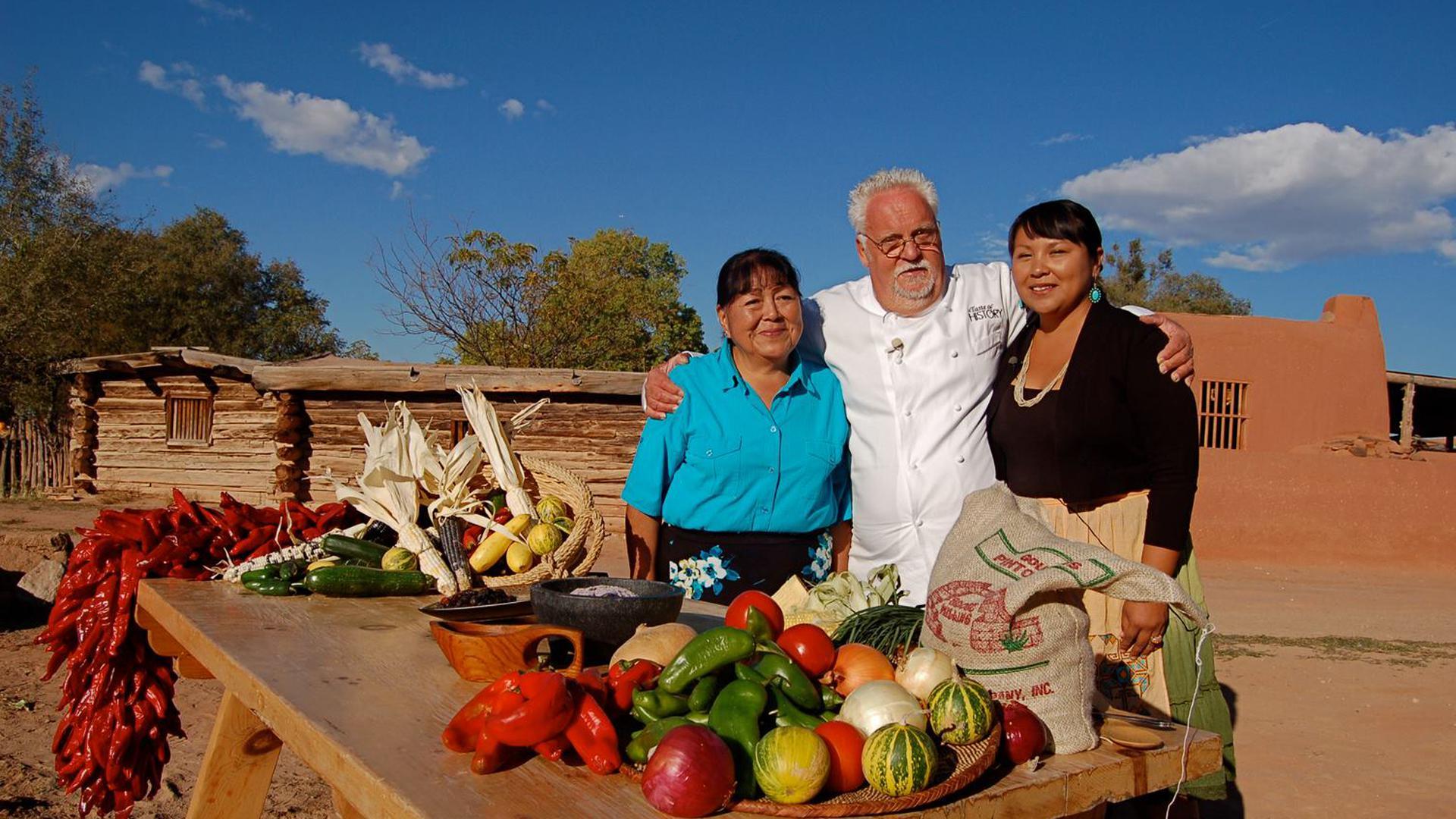 Ein Mann und zwei Frauen stehen Arm in Arm vor einem Tisch mit Gemüse und Obst.