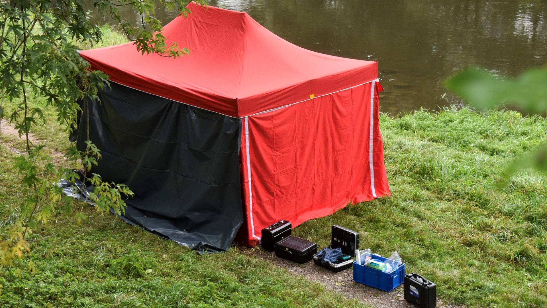 Spurensicherung am Enzufer: An der Fundstelle des Leichnams steht am Montagmittag ein Zelt der Kriminaltechnik des Pforzheimer Polizeipräsidiums.