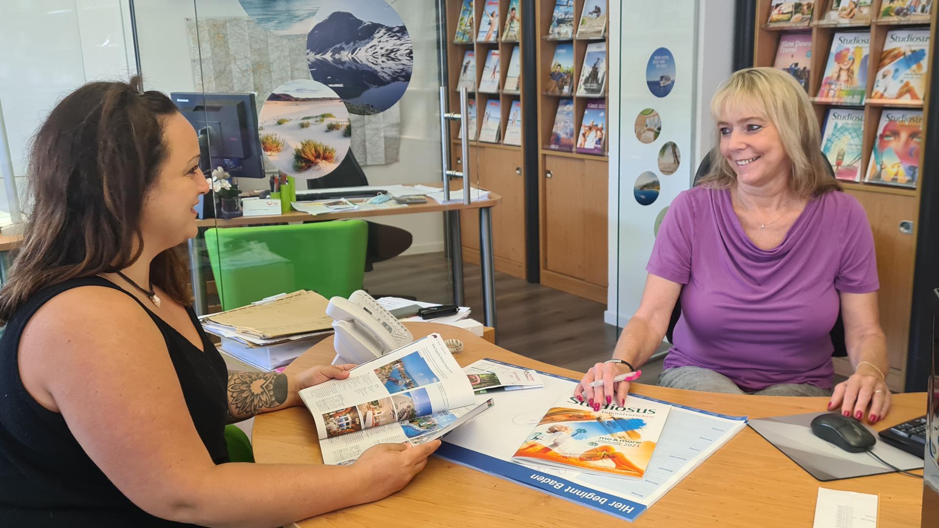 Zwei Frauen sitzen sich in einem Reisebüro gegenüber