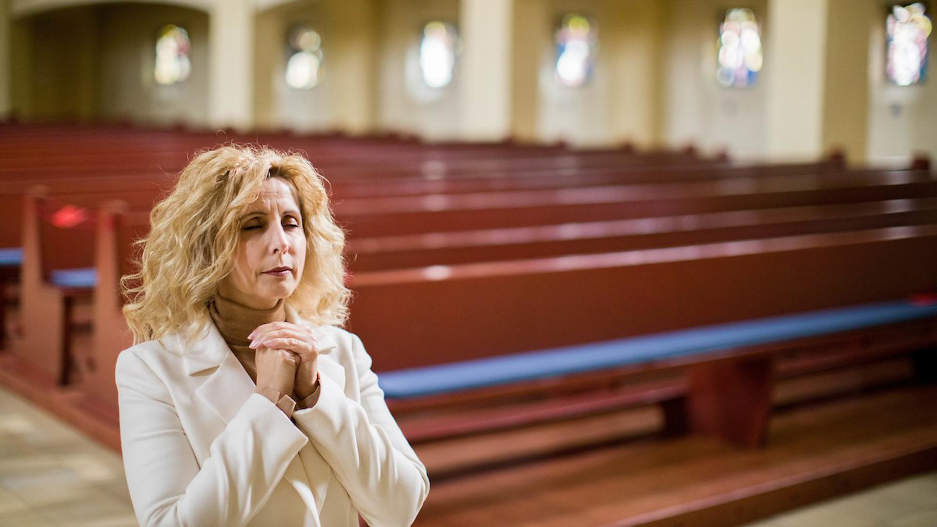 Eine Frau steht mit gefalteten Händen im Innenraum einer Kirche. Im Hintergrund sind Kirchenbänke.
