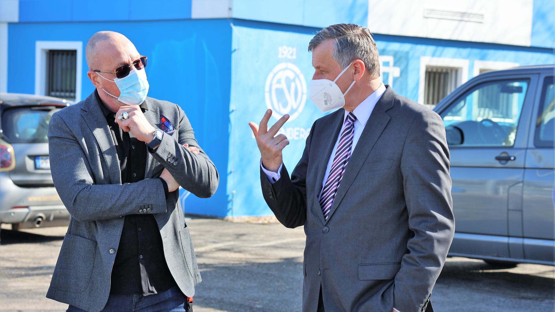 Mit Corona-Masken: Die Pforzheimer Stadträte Uwe Hück und Hans-Ulrich Rülke unterhalten sich engagiert auf dem Gelände des FSV Buckenberg im Stadtteil Haidach.