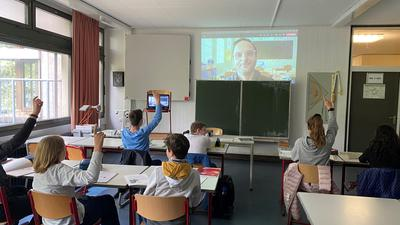 Lehrer ist an der Wand über Projektion zu sehen, Kinder heben die Hände in der Schulklasse.