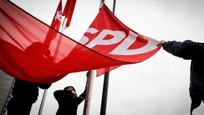 Fahnen mit dem SPD-Logo werden am 20.01.2018 vor der Parteitagshalle in Bonn (Nordrhein-Westfalen) im Regen hochgezogen.  CDU/CSU statt. Foto: Kay Nietfeld/dpa +++ dpa-Bildfunk +++   Verwendung weltweit