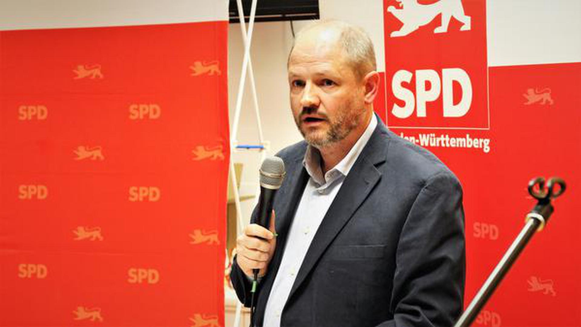 Ein Mann im Anzug steht mit Mikrofon vor einer rot-weißen SPD-Stellwand.