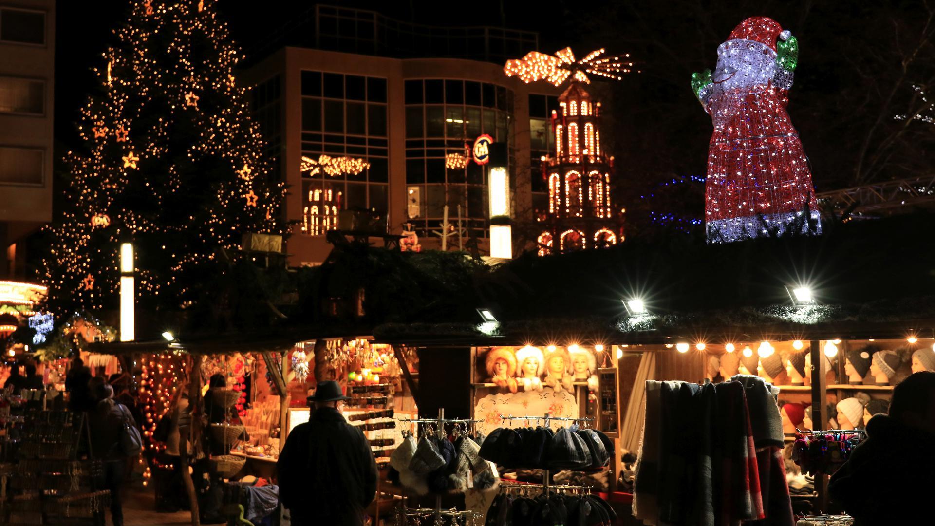 Besucher stehen an Ständen auf dem Weihnachtsmarkt in Pforzheim. Im Hintergrund sind ein geschmückter Weihnachtsbaum, die leuchtende Engels Pyramide und ein großer leuchtender Weihnachtsmann zu sehen.