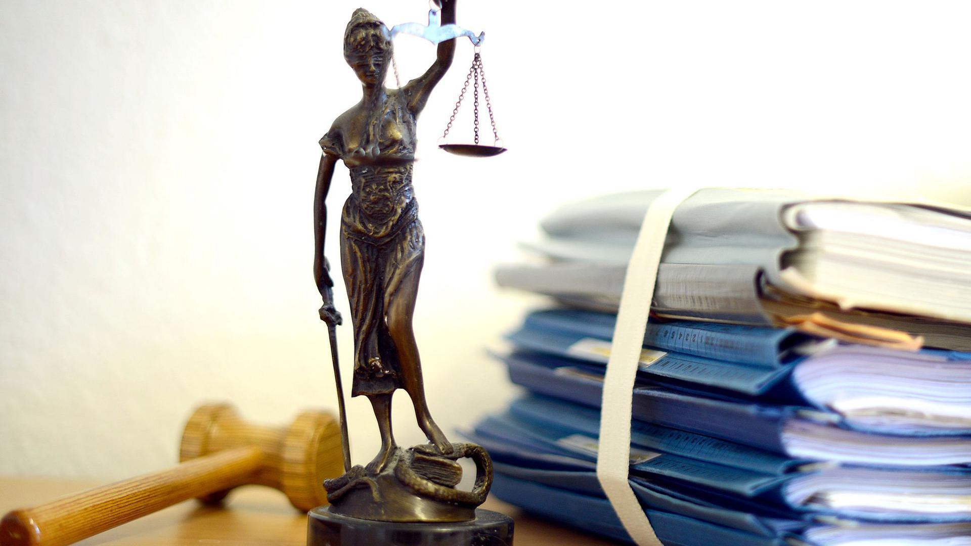 Die modellhafte Nachbildung der Justitia steht neben einem Holzhammer und einem Aktenstapel.