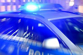 Ein Streifenwagen der Polizei steht mit eingeschaltetem Blaulicht auf der Straße.