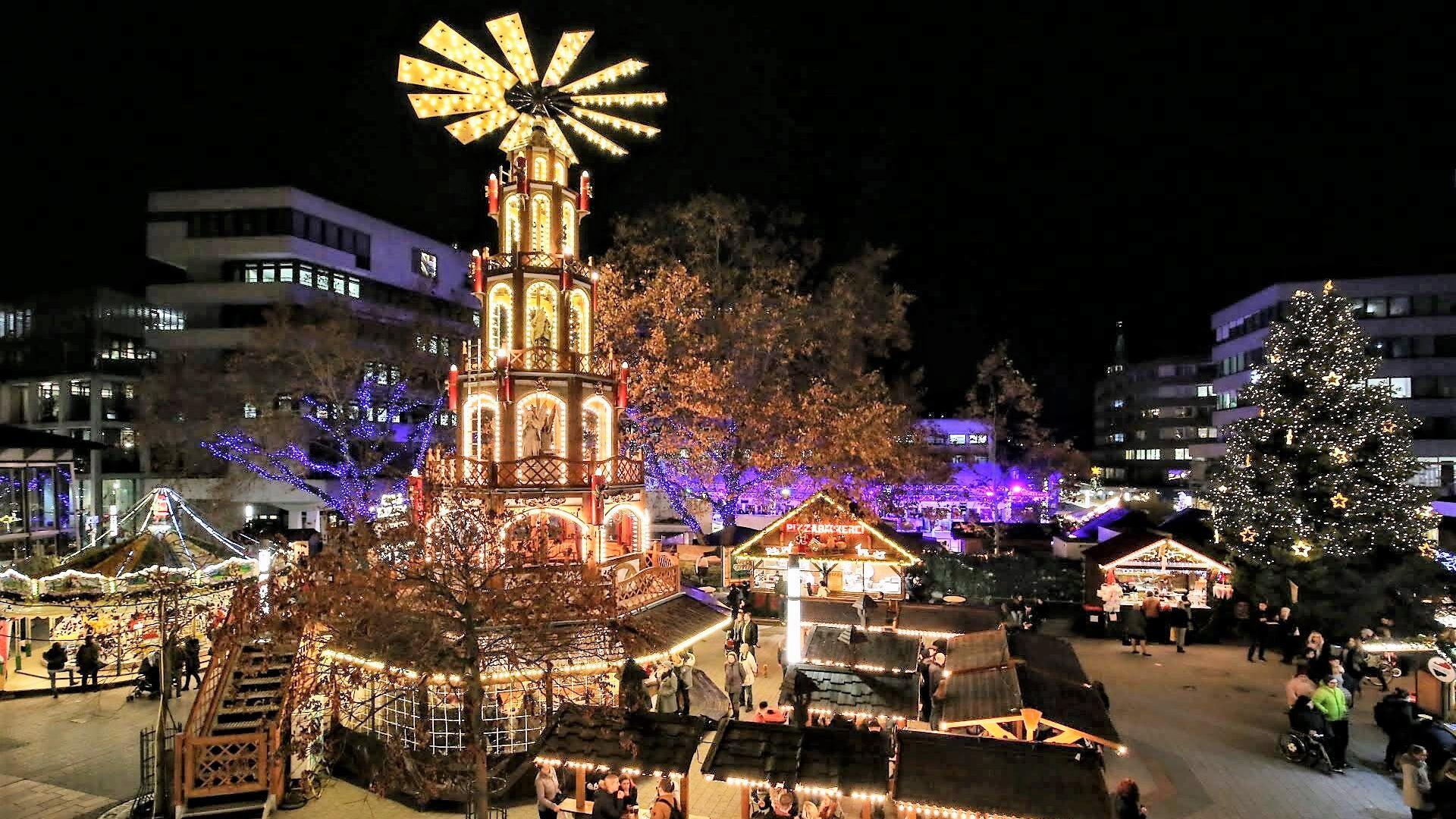Abendlicher Blick auf die leuchtende Engels Pyramide und die Stände auf dem Weihnachtsmarkt Pforzheim.