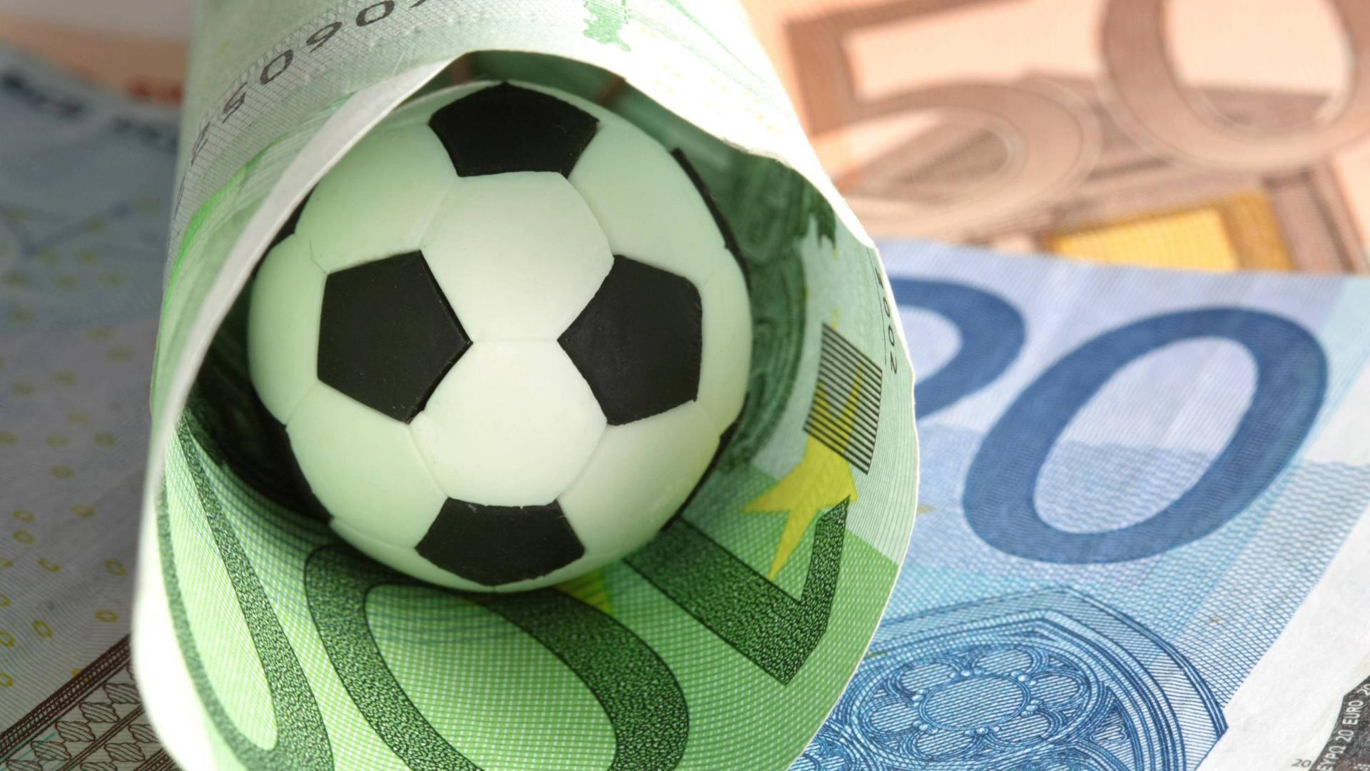 Wettskandal - Fußball liegt ein einem eingerollten 100 Euro Geldschein  Wettskandal Football is a a rolled 100 Euro Money