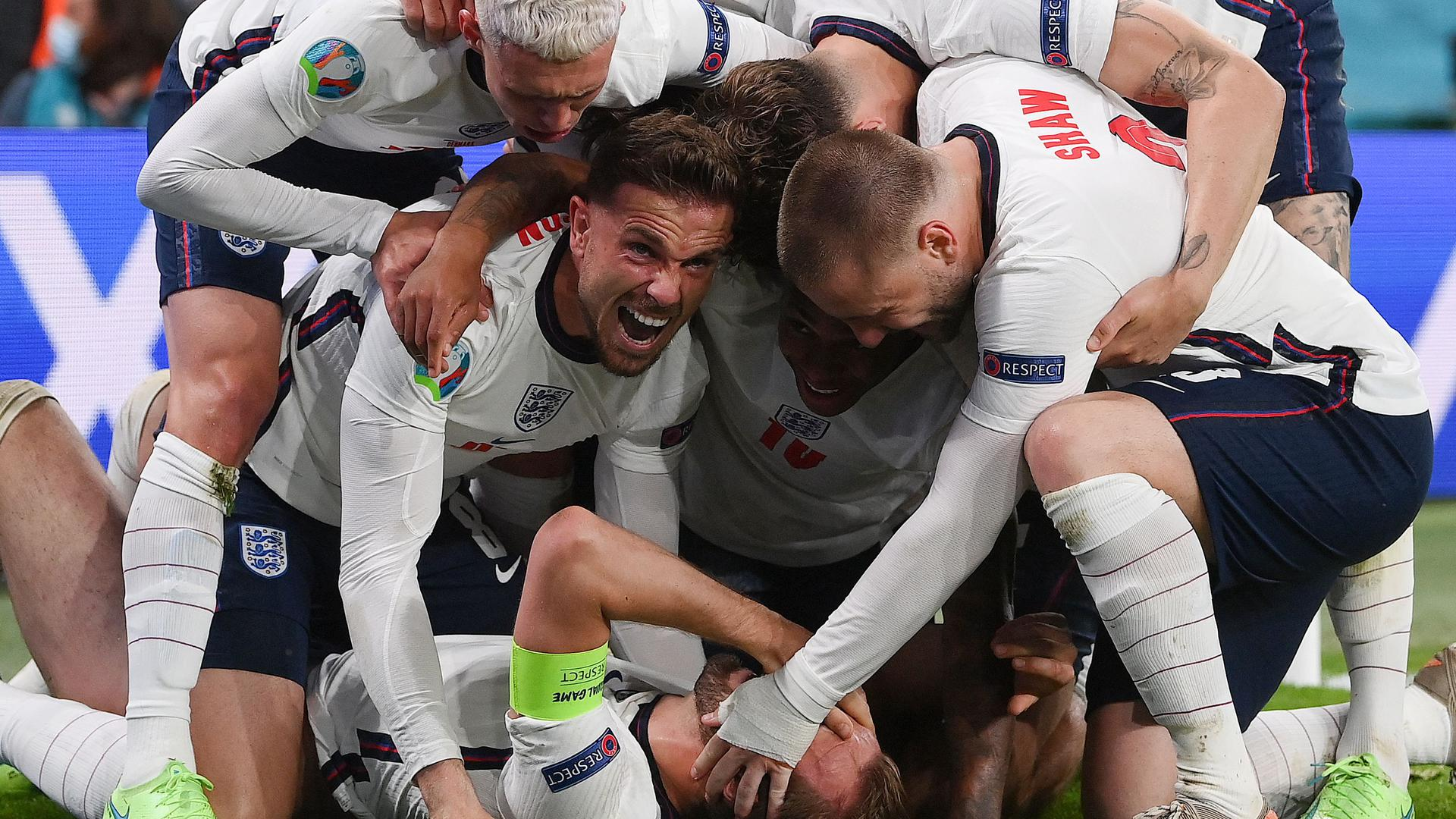 England's forward Harry Kane (bottom) celebrates with teammates after scoring a goal during the UEFA EURO 2020 semi-final football match between England and Denmark at Wembley Stadium in London on July 7, 2021. / AFP / POOL / Laurence Griffiths