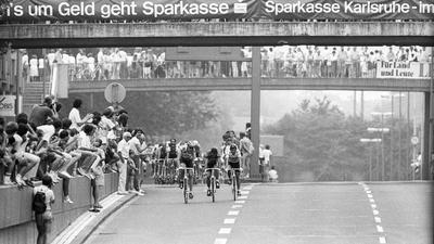 Das Feld der Tour de France auf der Kriegsstraße mit Zuschauern.