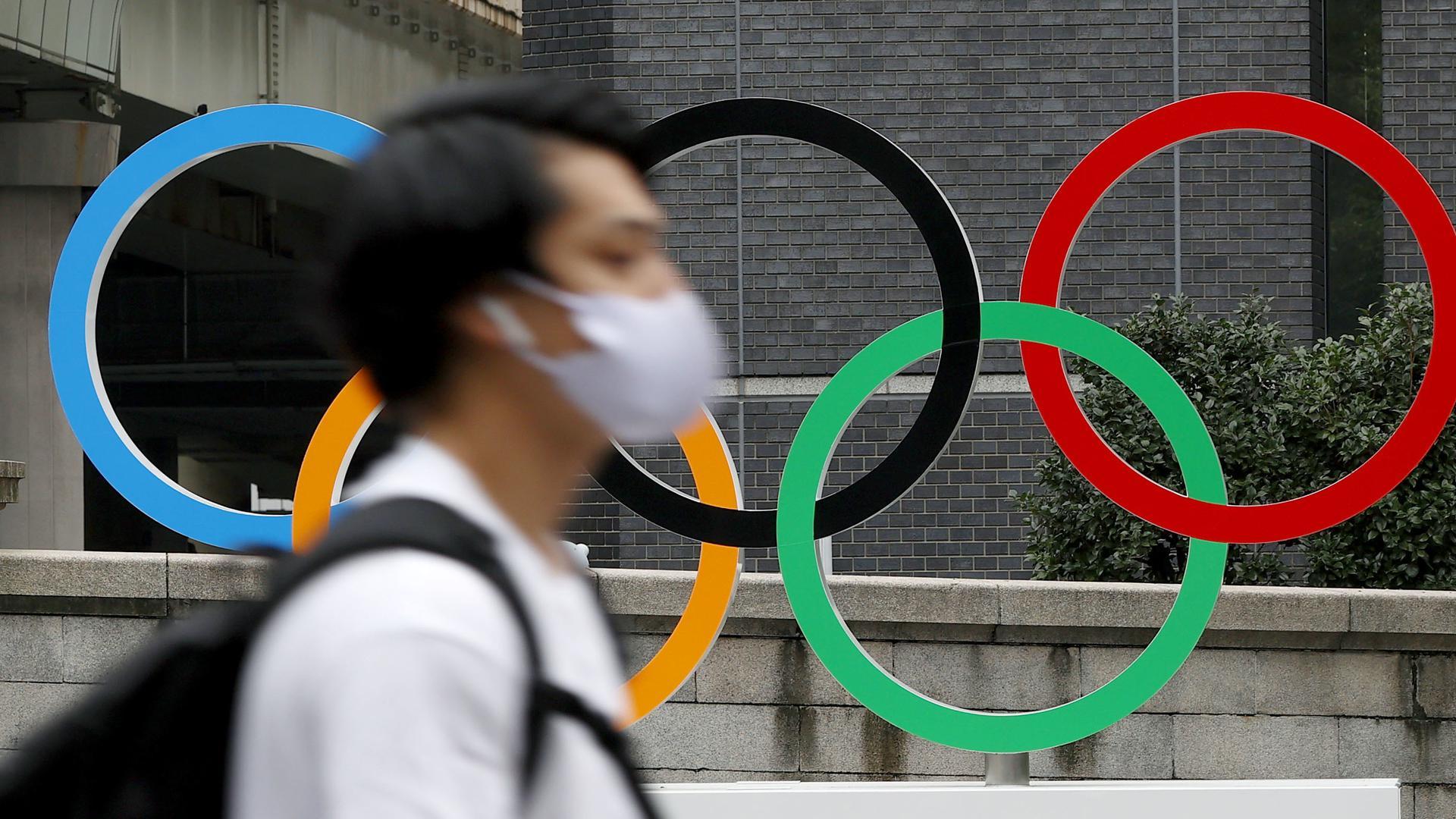 08.07.2021, Japan, Tokio: EinPassant geht mit Mund-Nasen-Schutz an einer Statue  mit übergroßen  OlympischenRinge vorbei. Während der Olympischen Spiele wird in Tokio erneut der Corona-Notstand herrschen. Der Notstand soll von kommendem Montag bis vorläufig zum 22. August gelten. Die Olympischen Spiele 2020 Tokio finden vom 23.07.2021 bis zum 08.08.2021 statt. Foto: ---/Kyodo/dpa +++ dpa-Bildfunk +++