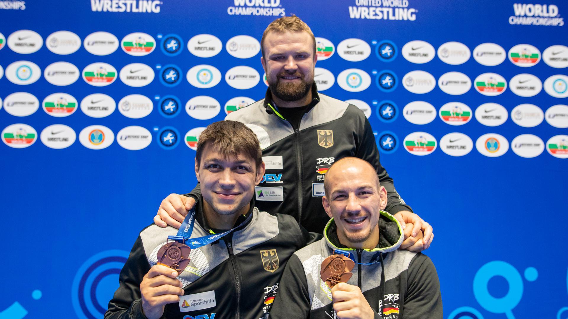 Denis Kudla (l), Frank Stäbler (r) und Eduard Popp (hinten) freuen sich über die Olympiaqualifikation. +++ dpa-Bildfunk +++