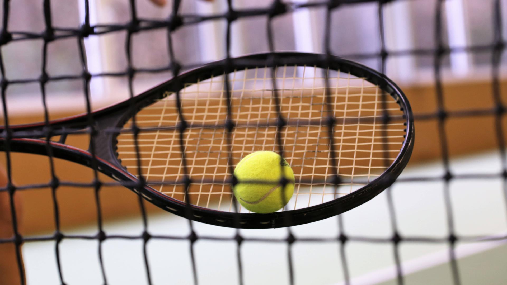 Symbolbild: Nahaufnahme von einem Tennisschläger mit Ball in einer Tennishalle *** Symbol image close-up of a tennis racket with ball in a tennis hall