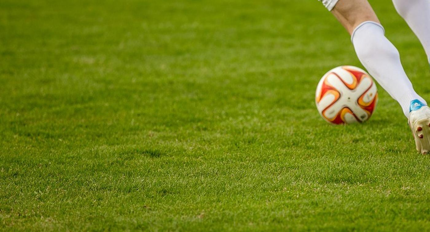 Ein Fußballspieler läuft mit Ball über einen Platz.