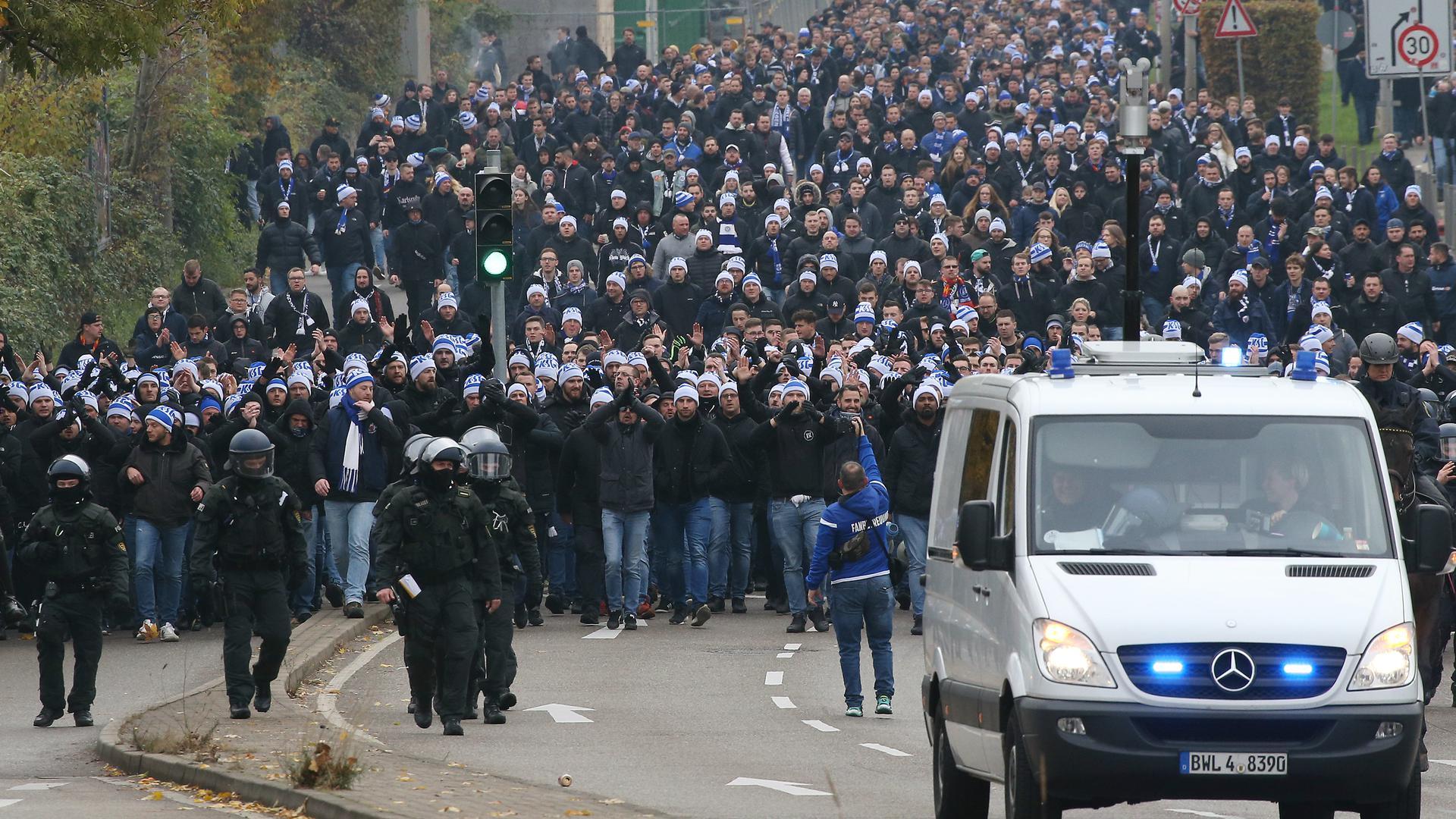 KSC-Fans stehen dicht zusammengedrängt vor Polizisten.