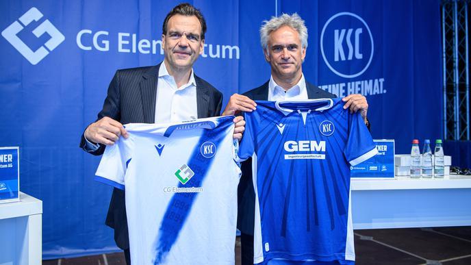 Christoph Groener, Vorstandsvorsitzender der CG Elementum AG, und KSC-Vizepräsident Martin A. Müller präsentieren das neue Auswärts- und Heimtrikot des KSC für die kommende Saison.