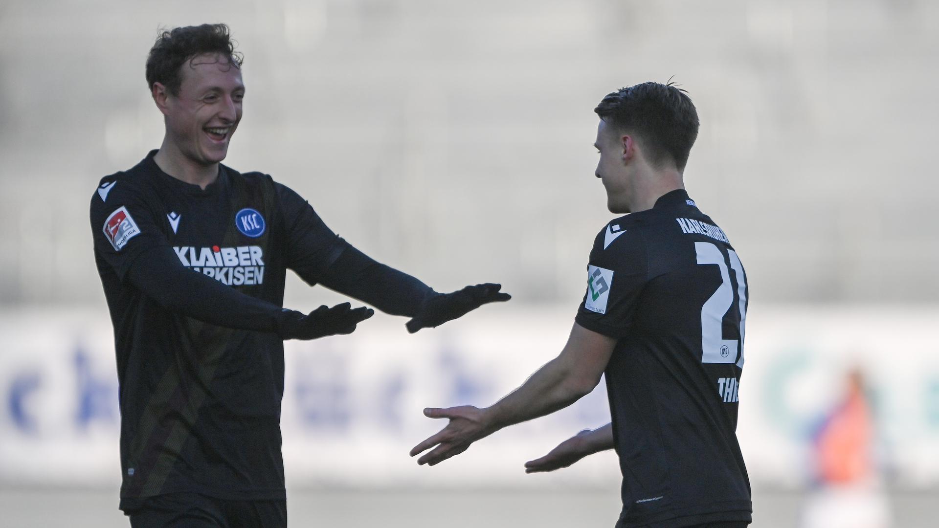 Toreverhinderer als Torjäger: Die KSC-Verteidiger Robin Bormuth und Marco Thiede (rechts) freuen sich diebisch über das 3:2 bei Holstein Kiel und ihre persönlichen Beiträge dazu.