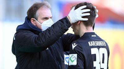Check am Spielfeldrand: Teamarzt Marcus Schweizer tastet den Kopf des KSC-Profis Benjamin Goller ab,  der am Sonntag nach der Pause unglücklich auf den Boden aufgekommen war.