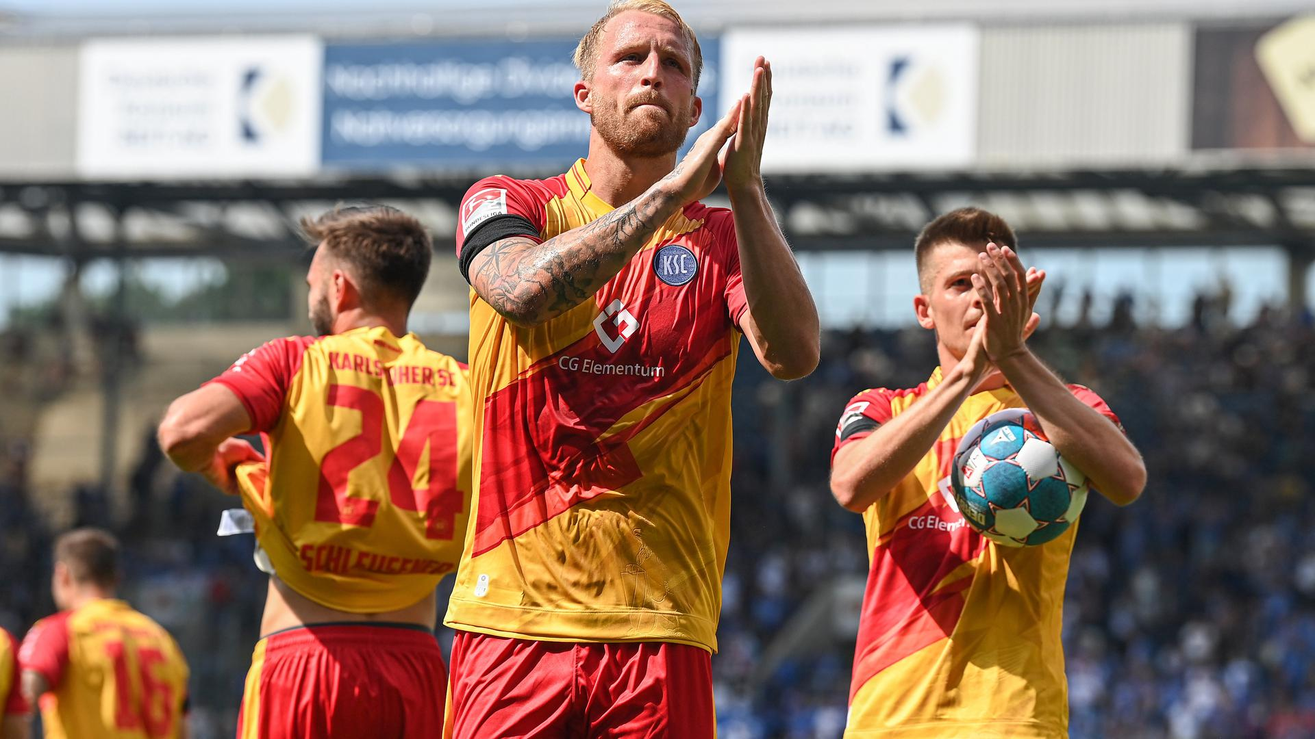 Aufatmen nach dem Auftakt: Philipp Hofmann und Marvin Wanitzek feiert mit mitgereisten KSC-Fans zum Saisonauftakt den 3:1-Sieg im Rostocker Ostseestadion.