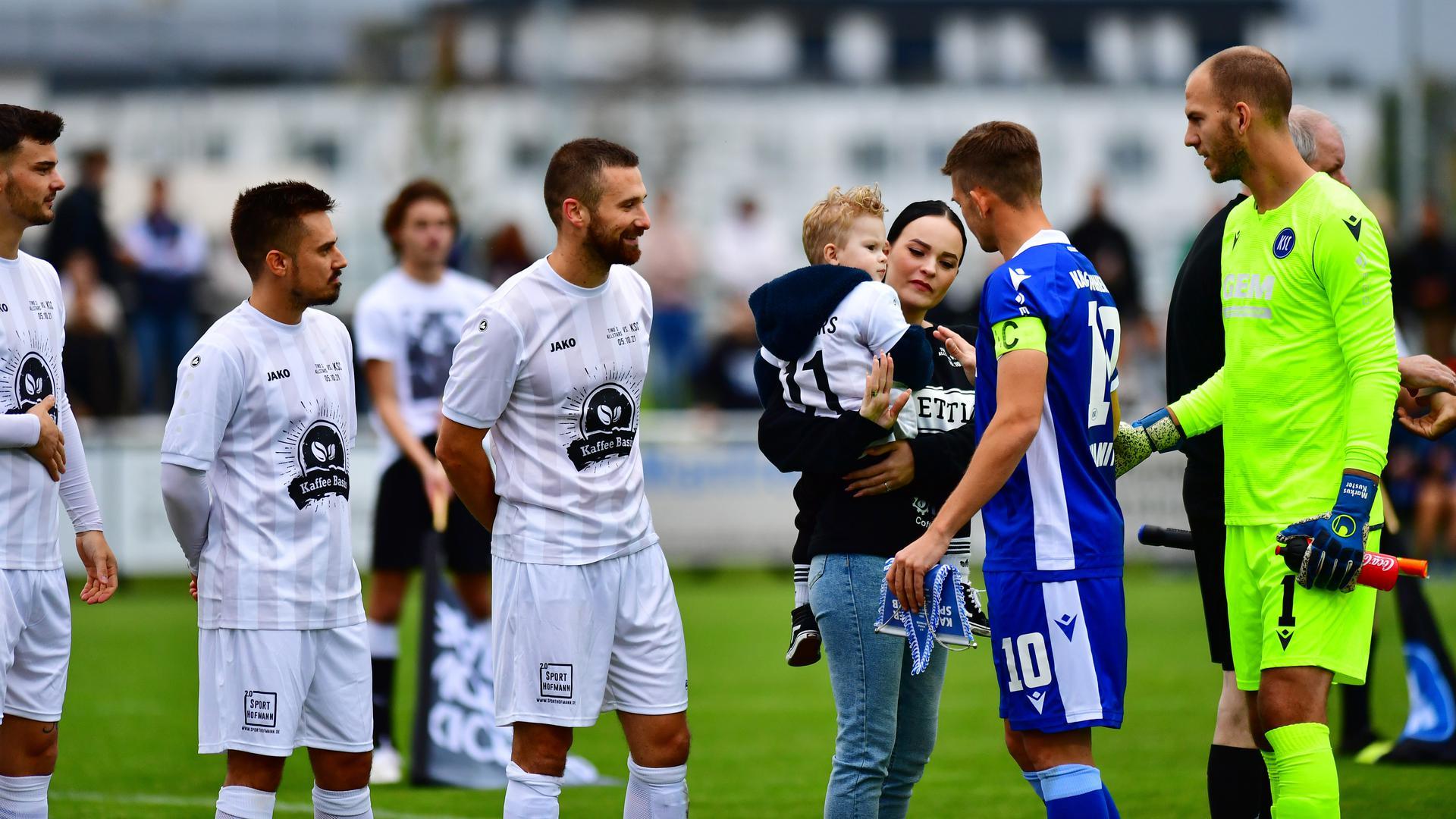 Emotionale Momente vor Anpfiff: Romina Hodzic geht mit Sohn Malik vom Platz. Der KSC um Marvin Wanitzek und Torwart Markus Kuster spielten danach gegen Amateure, um Geld für die Familie einzuspielen.
