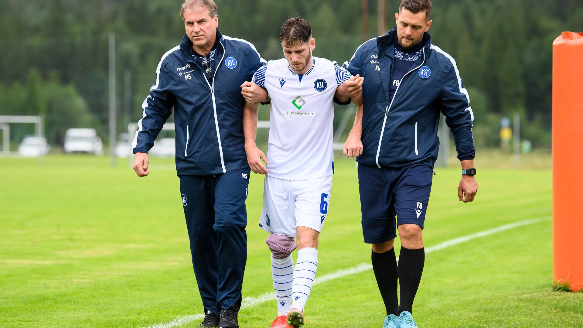 Mannschaftsarzt Dr. Marcus Schweizer (KSC) und Athletiktrainer Florian Boeckler (KSC) stuetzen den am rechten Knie Verletzten Leon Jensen (KSC).