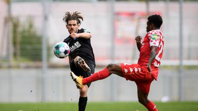 Debütant im KSC-Dress: Sebastian Jung (links), angegriffen vom Mainzer Abass Issah, spielt den Ball zu einem Mitspieler weiter.