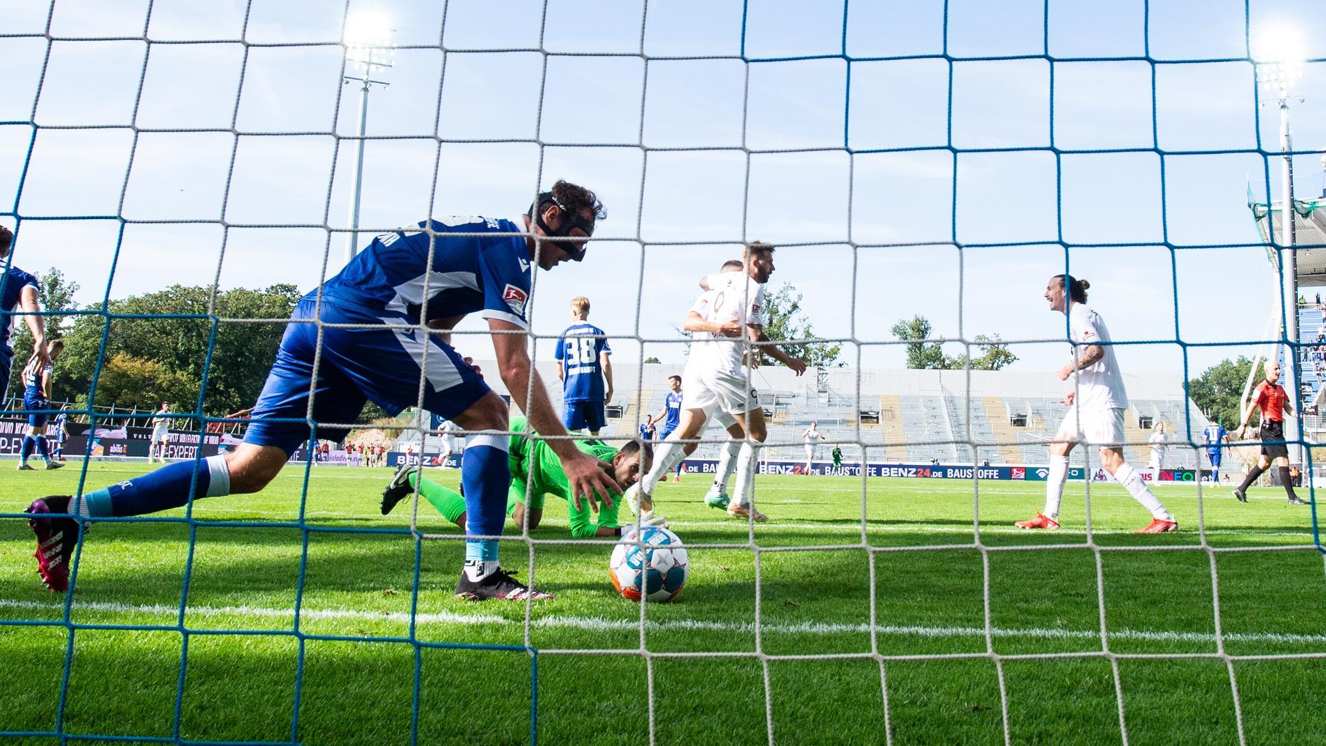 Robin Bormuth (KSC) holt den Ball nach Tor zum 0-3, hinten Torwart Marius Gersbeck (KSC) am Boden und jubelnde Spieler von St. Pauli.  GES/ Fussball/ 2. Bundesliga: Karlsruher SC - FC St. Pauli, 25.09.2021 --  Football/ Soccer 2rd Division: Karlsruher SC vs SC St. Pauli, Karlsruhe, Sep 25, 2021 --