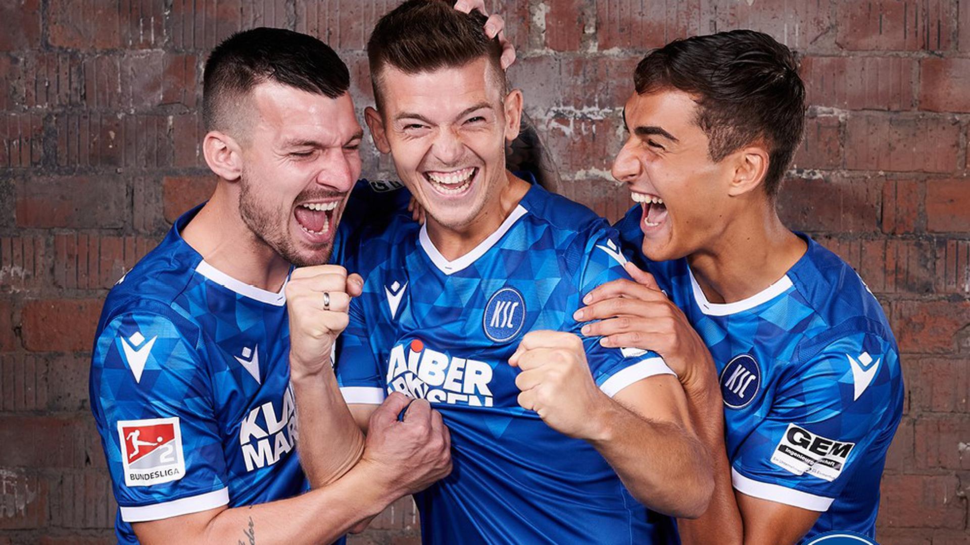 Drei Männer tragen das neue Trikot des KSC.