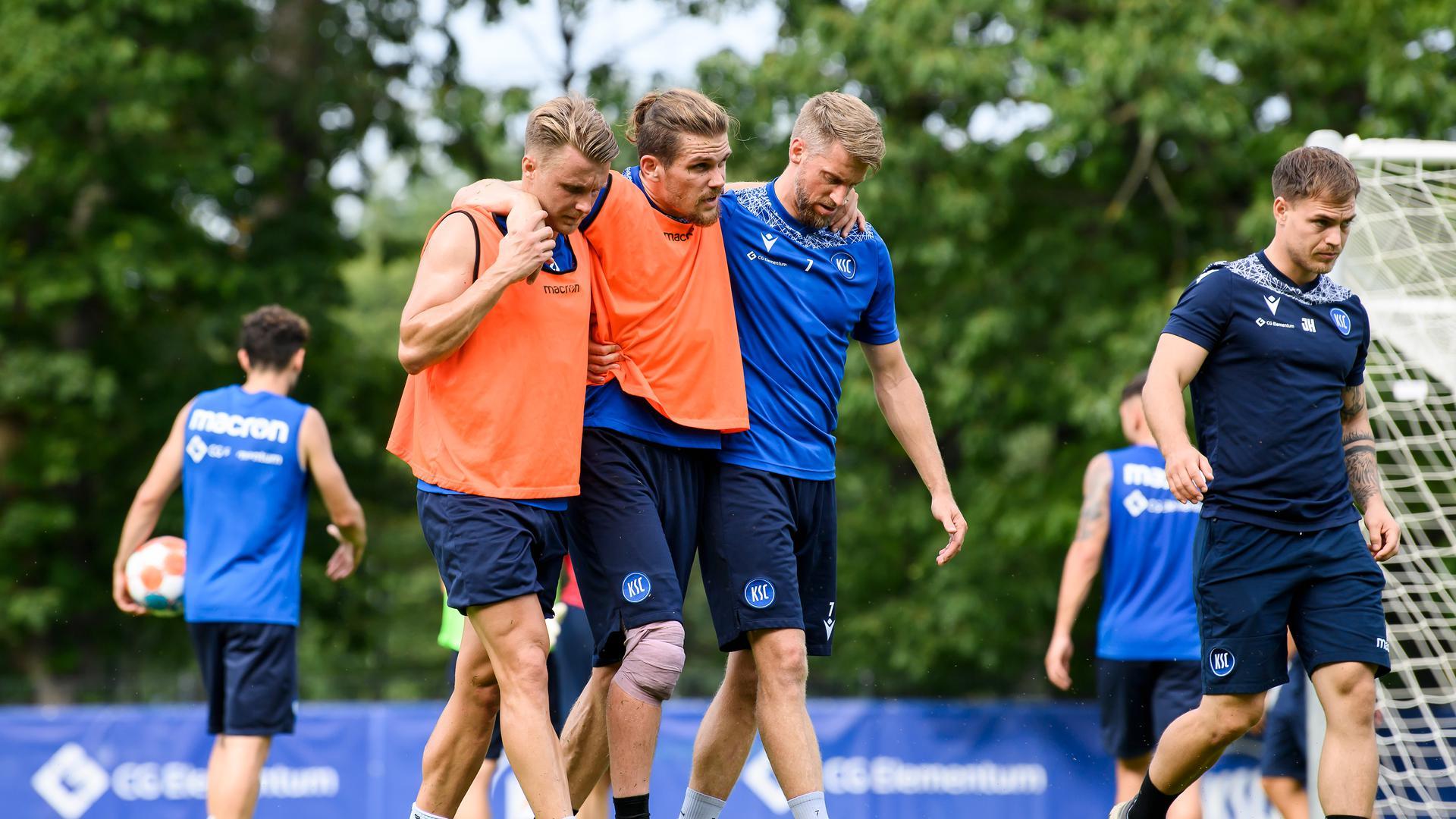 Kurz vor Ende der Trainingseinheit verletzte sich Sebastian Jung (KSC) am rechten Knie und musste von Marco Thiede (KSC) und Marc Lorenz (KSC) gestuetzt den Platz verlassen. Rechts: Physiotherapeut Johannes Haberlandt (KSC).  GES/ Fussball/ 2. Bundesliga: Karlsruher SC - Training, 14.09.2021  Football/Soccer: 2. Bundesliga: KSC Training, Karlsruhe, September 14, 2021