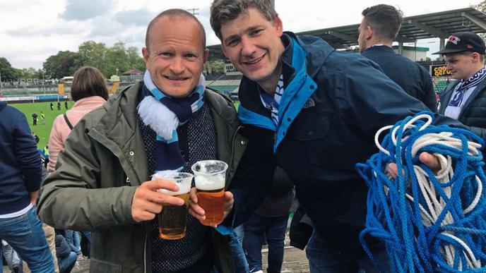"""Nico Niederberger und Ingo Freese (von links) aus Ettlingen haben das Aufstiegsband in der Hand, das die Ordner zur Absperrung nutzten. """"Es ist blau-weiß und hält uns zusammen"""", sagt Freese. Er sagt dieses Aufstiegsdelikt sei besser als Rasen oder ein 11-Meter-Punkt. Sie feiern den Sieg heute Abend bei Freunden in Münster."""