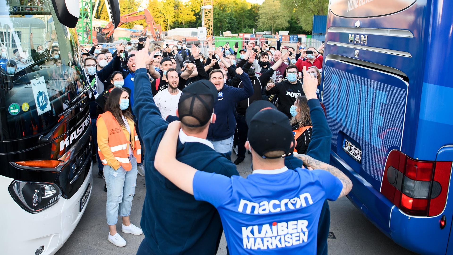 Begegnung mit Fans: Philipp Hofmann und Markus Kuster zeigen sich nach dem Ausstieg aus dem Bus vor dem Wildparkstadion den auf die Mannschaft wartenden Anhängern.