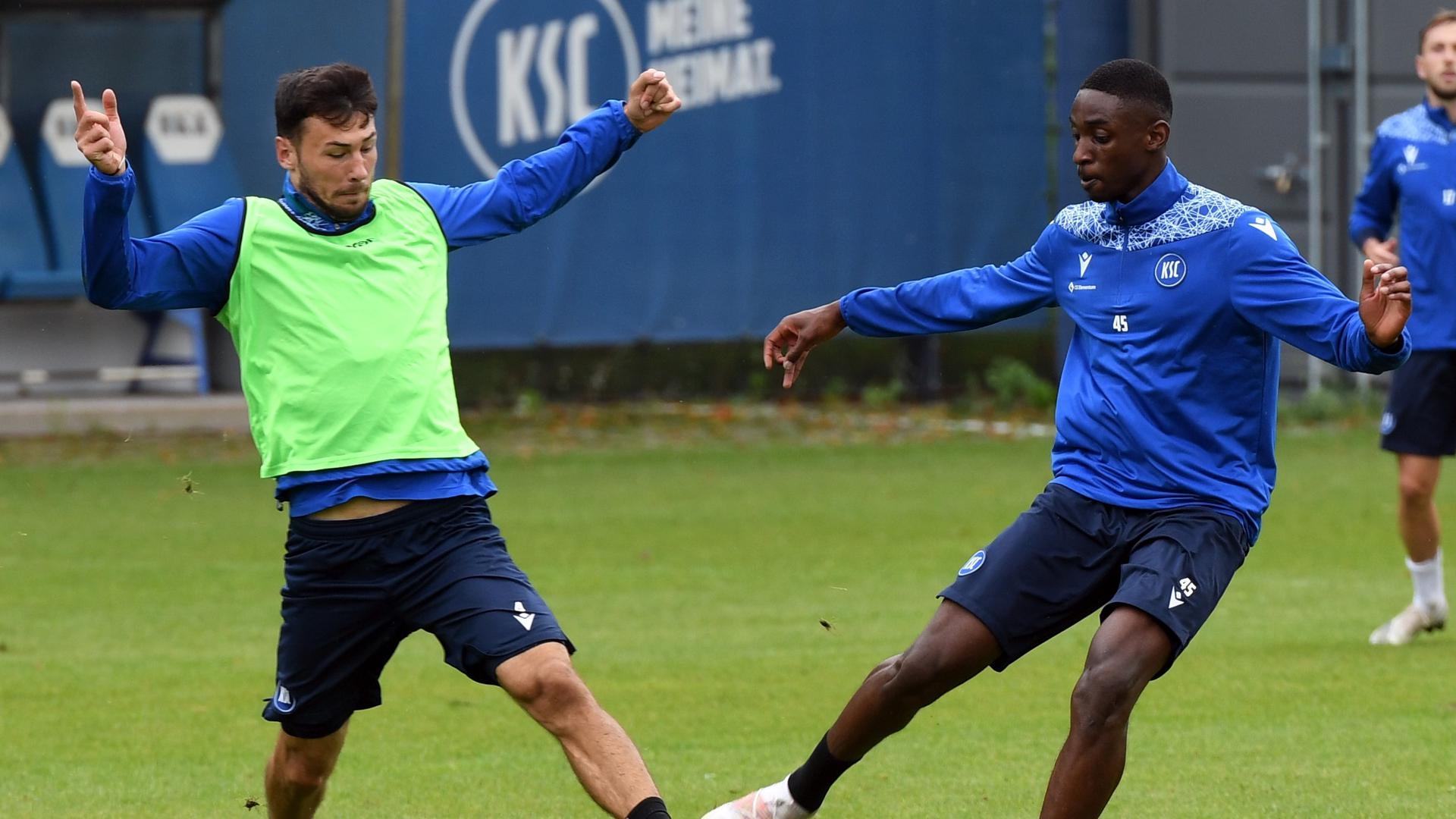 Kommen und Gehen: Lukas Fröde bemüht sich am Montagvormittag im KSC-Training gegen Felix Iroerere (rechts) um  den Ball.