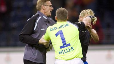 Faustkampf unter Kollegen: Markus Miller und Bradley Carnell gehen sich nach dem 1:0-Sieg des KSC in Frankfurt an die Wäsche. Torwarttrainer Peter Gadinger (links) muss schlichten.