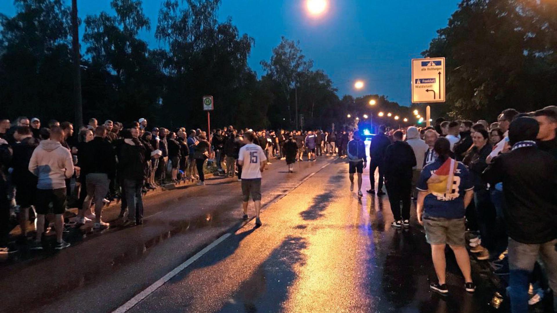KSC-Fans warten auf der Straße vor dem Wildparkstadion auf die Ankunft der Mannschaft.