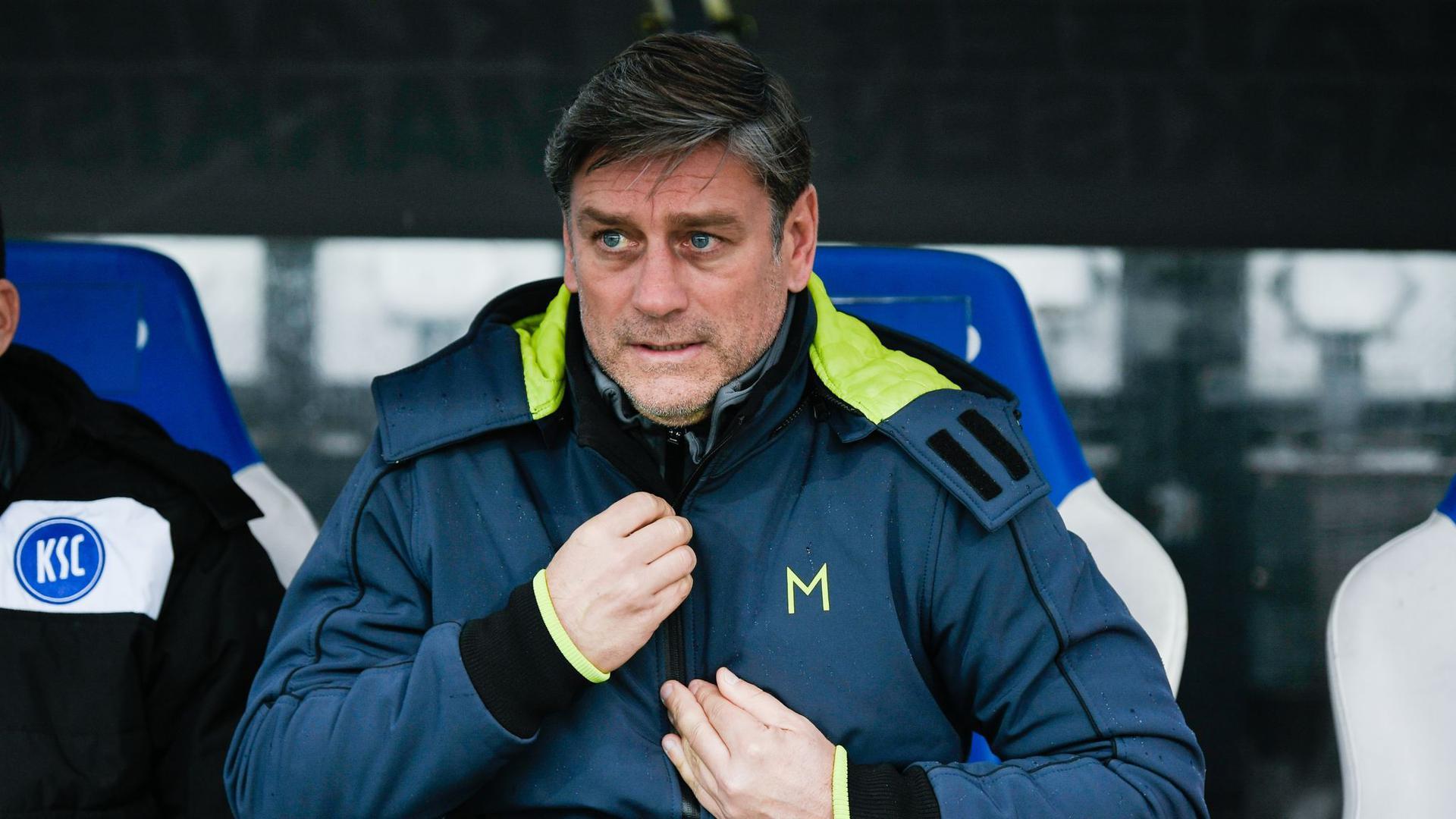 Der Karlsruher Sportdirektor Oliver Kreuzer sitzt auf der Bank.