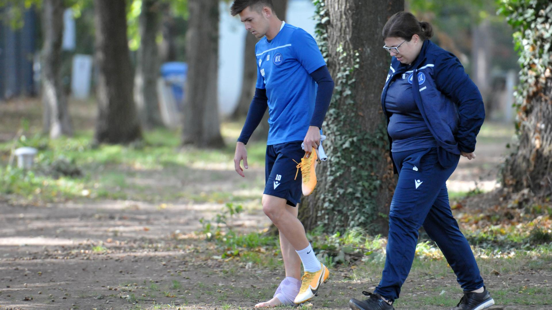 Schmerzhafter Feierabend: Marvin Wanitzek verlässt am Dienstagnachmittag den Trainingsplatz mit Physiotherapeutin Julia Born in Richtung Mannschaftsarzt.