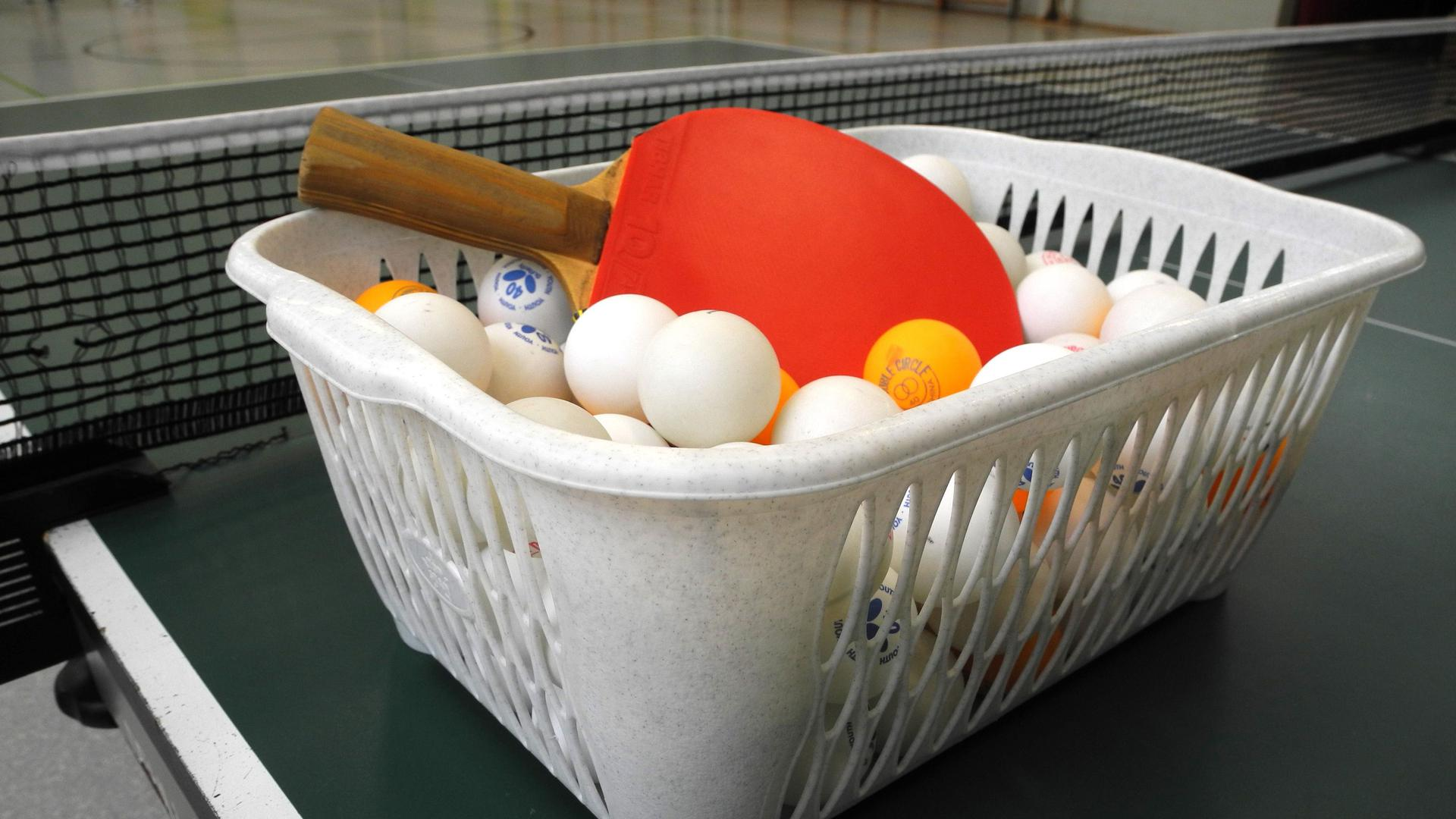 Das Bild zeigt einen kleinen Korb mit einem Tischtennis-Schläger und Bällen